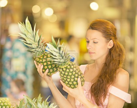 Woman shopping in supermarket, fruit section