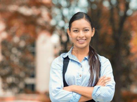 Foto de Retrato de primer plano, joven profesional, hermosa mujer de negocios confiada en camisa azul sonriendo aislado fondo árboles al aire libre. Emociones humanas positivas, expresiones faciales, actitud, percepción de la vida - Imagen libre de derechos