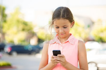 Photo for Closeup portrait happy, cheerful, girl, excited by what she sees on cell phone isolated outdoor street background. Positive Facial expressions, reaction. Teenager sending text message from her mobile - Royalty Free Image