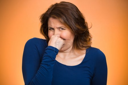 Woman pinches her nose, bad smell