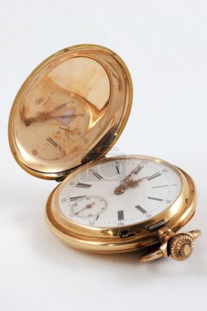 Pocket watch in a gold case on a white background, zoom