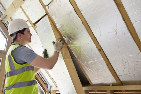 Foto de Constructor de montaje de aislamiento en el techo de la nueva casa - Imagen libre de derechos