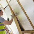 Builder Fitting Insulation Into Roof Of New Home...