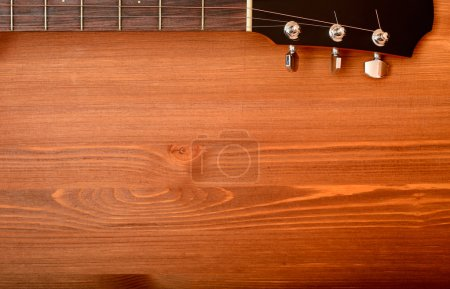 Close-up western guitar neck on wooden background
