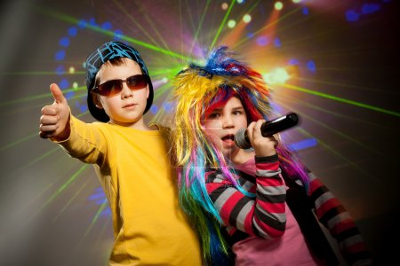 Photo for Little children singing, dancing in disco club - Royalty Free Image