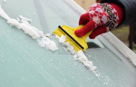 Photo pour Main de femme en gant raclant la glace et la neige du pare-brise de voiture - image libre de droit