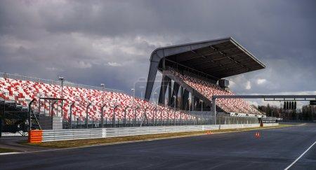 Photo pour Tribune géante avec sièges colorés sur piste de Formule 1 - image libre de droit