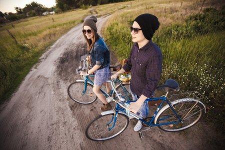 Photo pour Deux jeunes branchés belles, debout en plein air en été avec des engins fixes vintage blanc vélo - image libre de droit