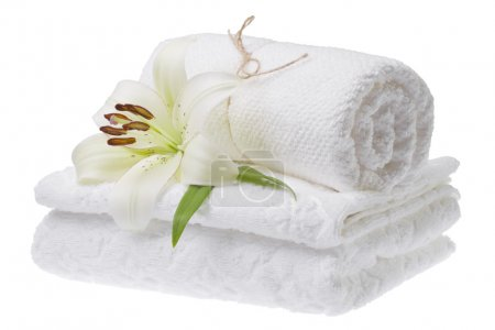 Stack of white towels with lily