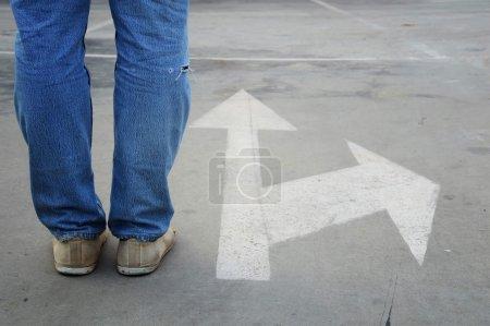 Foto de Zapatillas hombres con los pantalones vaqueros en la carretera asfaltada con flecha blanca dirección, concepto de tomar una decisión en el cruce - Imagen libre de derechos