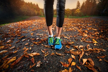 Photo for Young woman running in the early evening autumn leaves - Royalty Free Image