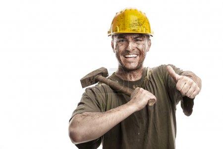 Foto de Sucio sonriente trabajador joven con casco casco - Imagen libre de derechos