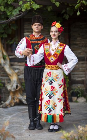 Photo for Young man and beautiful woman dressed in antique traditional Bulgarian hand-embroidered folk costumes. - Royalty Free Image