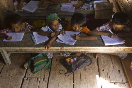 Photo pour Image prise en verser un peu dans un village au myanmar, où des âges différents od enfants étudient différentes questions. - image libre de droit