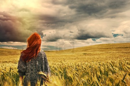 Photo for Fashion young red hair woman standing back outdoor on breathtaking view of dramatic storm sky in the field - Royalty Free Image