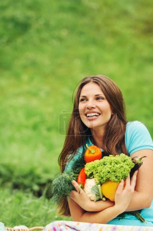 Photo for Cute happy woman with organic healthy fruits and vegetables on the picnic in the park outdoors - Royalty Free Image