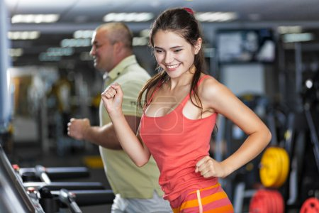 Photo for Sportive woman and man are running on treadmill in a gym - Royalty Free Image
