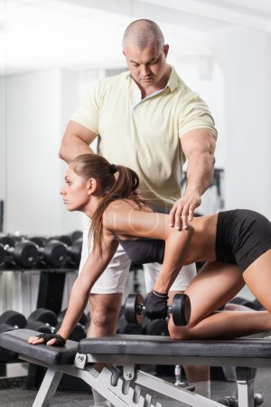 Photo for Woman at the health club with her personal trainer, learning the correct form with barbell - Royalty Free Image