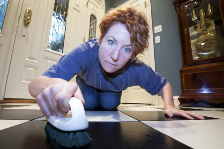 Photo for Close up view of a woman scrubbing the floors on her hands and knees. - Royalty Free Image