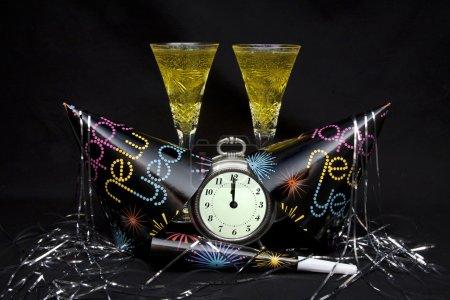 Foto de Sombreros de fiesta de año nuevo, generador de ruido y serpentina con reloj mostrando medianoche y dos flautas de champán. - Imagen libre de derechos
