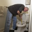 Man with plunger fixing blocked toiler...