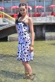 Krásná asijská žena v mokrých šatech pózuje v kašně