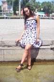 Krásné asijské ženy v mokrých šatech a mokré hnědé vlasy sedí se uklonil nohy v kašně