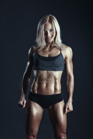 Fitness young woman standing on dark background. M...