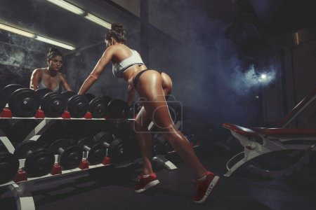 Photo for Photo of sexy young woman resting in the gym and leaning on row - Royalty Free Image