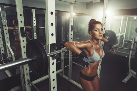 Photo for Woman resting after lifting barbells - Royalty Free Image