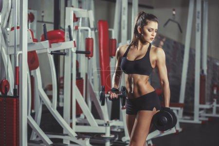 Photo pour Fille sexy avec des haltères dans la salle de gym - image libre de droit