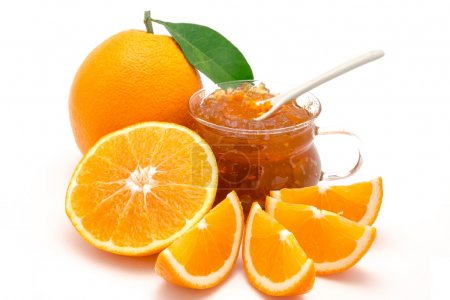 Oranges whole and sliced together with orange jam in a recipient, isolated on a white background