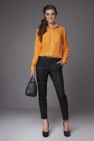 Beautiful sexy young business woman with evening makeup dressed in tight pants silk blouse with lace long sleeves high-heeled shoes and a small black handbag, business clothes for meetings and walks