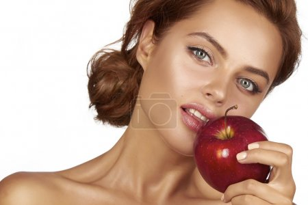 Young beautiful sexy girl with dark curly hair, bare shoulders and neck, holding big red apple to enjoy the taste and are dieting, healthy eating and organic foods, feeling temptation, smile, teeth