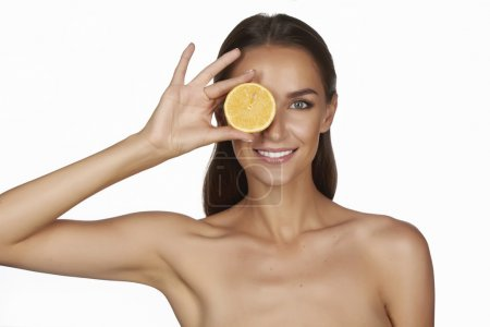 Photo for Beautiful sexy young woman with perfect healthy skin and long brown hair day makeup bare shoulders holding orange lemon grapefruit healthy eating organic food diet weight loss - Royalty Free Image