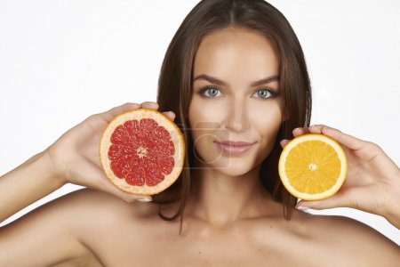 Beautiful sexy young woman with perfect healthy skin and long brown hair day makeup bare shoulders holding orange lemon grapefruit healthy eating organic food diet weight loss