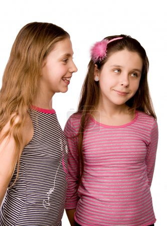 Two girls in the age of ten and eleven sharing ideas