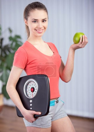 Photo for Healthy diet eating woman with scale and apple for weightloss - Royalty Free Image