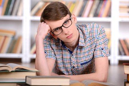 Photo pour Portrait d'étudiant habile avec le livre ouvert, lire dans la bibliothèque du Collège - image libre de droit