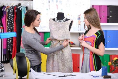 Photo pour Créateurs de mode au travail. deux jeunes femmes gaies travaillant au studio de design de mode - image libre de droit