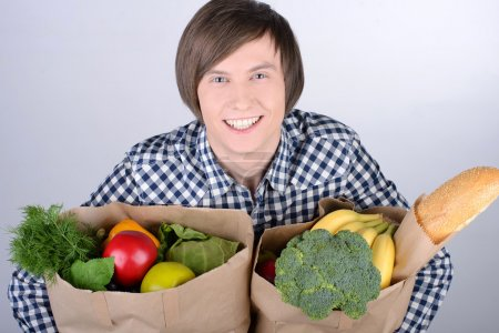 Photo for Smiling young man holding shopping bag full of groceries on white - Royalty Free Image