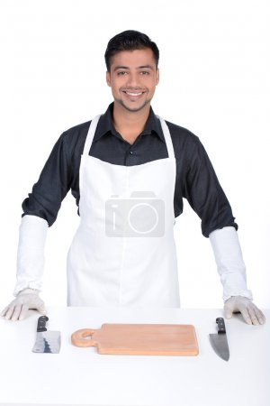 Photo for Man wearing apron holding knife. handsome butcher smiling and holding knife - Royalty Free Image
