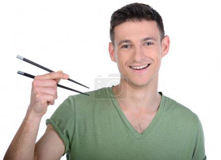 Photo pour Un homme qui mange des sushis. Joyeux jeune homme mangeant des sushis tout en se tenant isolé sur blanc - image libre de droit
