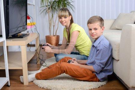 Photo pour Une belle femme et son fils adolescent à la maison, assis sur un canapé jouant à un jeu vidéo . - image libre de droit