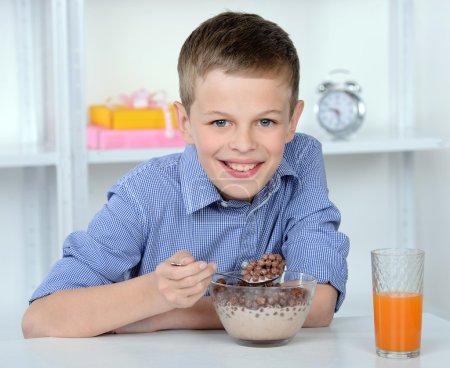 Photo pour Portrait d'un jeune garçon souriant profitant du petit déjeuner dans la cuisine à la maison - image libre de droit