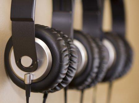 Photo pour Photo horizontale de trois paires d'écouteurs suspendus avec fond beige - image libre de droit